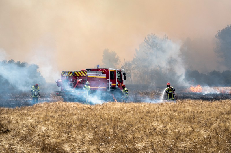 Sioen - Four firemen are extinguishing a bush fire using a fire engine and fire hoses