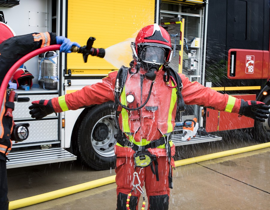 Sioen - a firefighter in full suit is rinsed using a fire hose