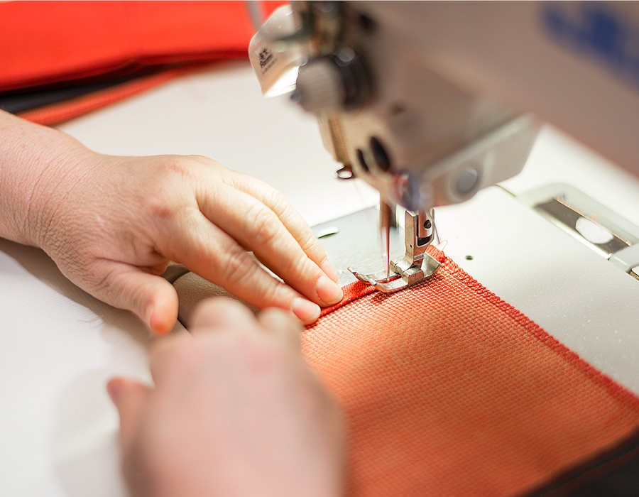 Sioen - a seamstress is using a sewing machine