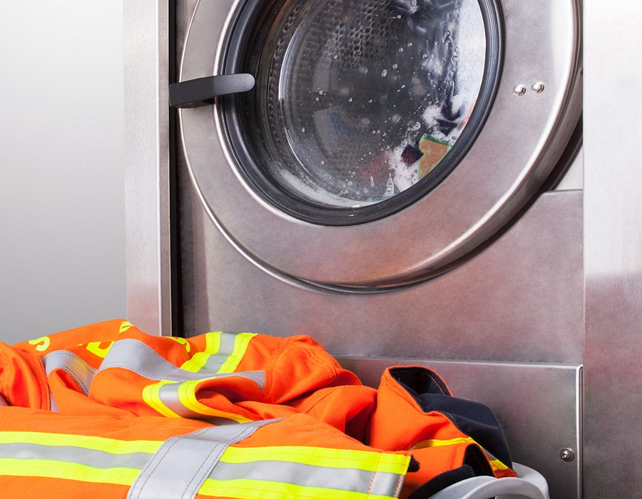 Sioen - Firefighter garments in front of a working washing machine