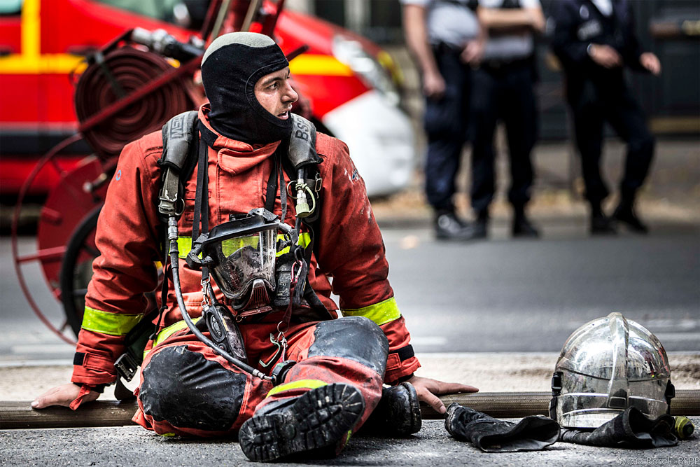 Sioen: A tired firefighter is sitting on the ground in full firefighter garments after an intervention